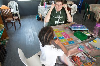Eine Schülerin übt die Buchstaben zusammen mit einer freiwilligen Lehrer/in