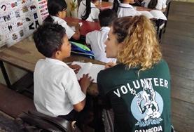 Eine Freiwillige im Unterrichts - Projekt spricht mit einem Schüler in der lokalen Sprache Khmer.