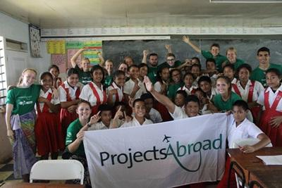 Freiwillige posen mit ihren Schülern für ein Gruppenbild